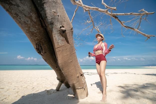 Kobieta w bikini stojąca na białej, piaszczystej plaży. błękitny krajobraz morza i nieba. letni wypoczynek.