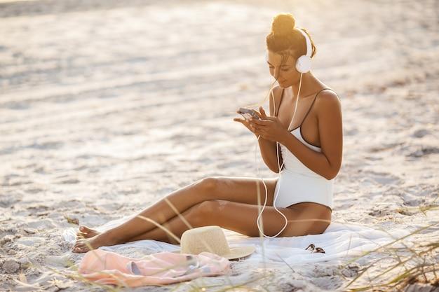 Kobieta w bikini ze smartfonem i słuchawki na plaży