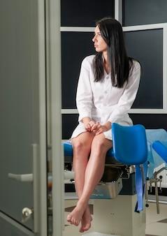 Kobieta w biurze ginekologa siedzi i czeka na lekarza z wynikami badań, widok przez drzwi