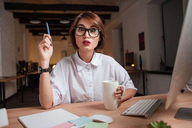 Kobieta w biurze ma pomysł. patrząc w kamerę