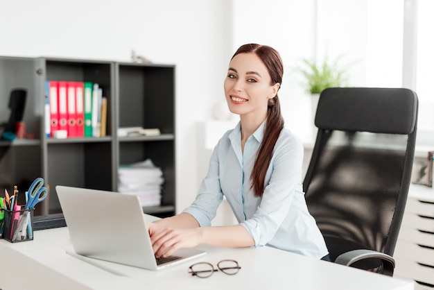 Kobieta w biurze przy biurku z laptopu ono uśmiecha się