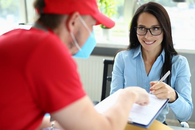 Kobieta w biurze przyjmuje przesyłkę od kuriera w masce medycznej.