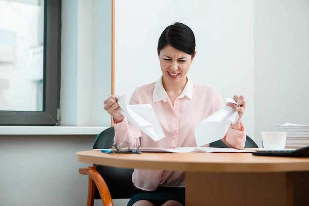 Kobieta w biurze z zmiętym papierem. koncepcja życia biura.