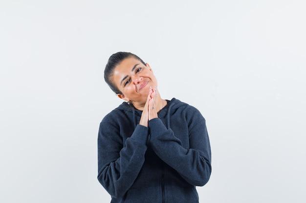 Kobieta w bluzie z kapturem pokazująca gest namaste i wyglądająca z nadzieją, widok z przodu.