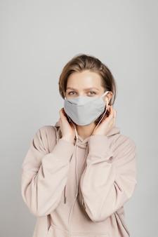 Kobieta w bluzie z kapturem z maską