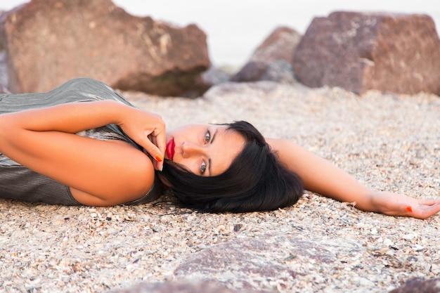 Kobieta w błyszczącej srebrnej sukience leży na kamieniach na plaży morskiej,