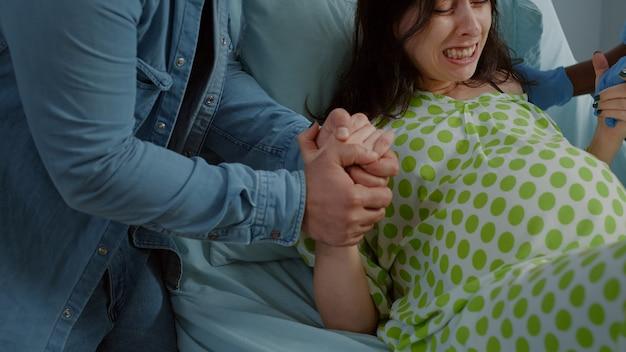 Kobieta w bólu od porodu trzymająca się za ręce z mężem