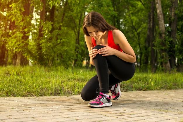 Kobieta w bólu podczas gdy biegający w parku