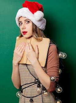 Kobieta w bożenarodzeniowym kapeluszu i rocznik rezerwujemy na zieleni ścianie