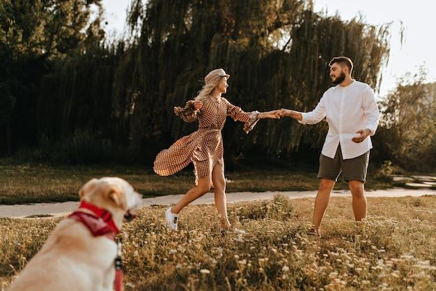 Kobieta w brązowej sukience i czapce oraz mężczyzna w szortach i koszuli wygłupiają się w parku, spacerując z psem.