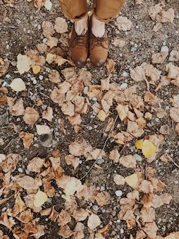 Kobieta w brązowych butach i beżowych spodniach stojących na suszonych liściach