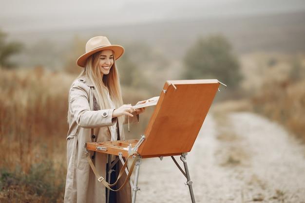 Kobieta w brązowym płaszczu malowanie w polu