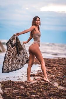 Kobieta w brązowym stroju kąpielowym i sarongu na naturalnym tle obok skał i morza