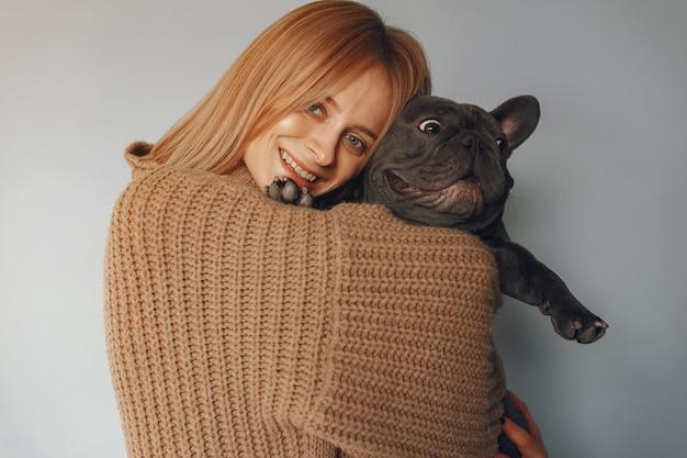 Kobieta w brązowym swetrze z czarnym buldogiem
