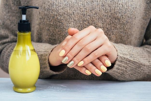 Kobieta w brown puloweru seansu rękach z żółtym manicure'em, zakończenie