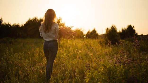 Kobieta w cajgach i białej koszulowej pozyci na polu