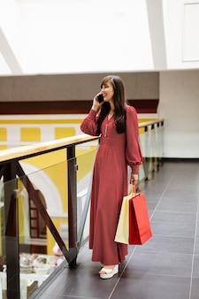 Kobieta w centrum handlowym rozmawia przez telefon, trzymając torby na zakupy