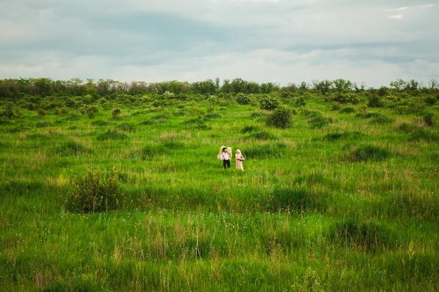 Kobieta w chustce i mężczyzna chodzący po łące