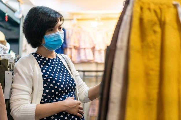 Kobieta w ciąży azjatyckich nosić maskę na zakupy do odzieży w butiku