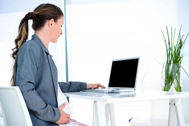 Kobieta w ciąży biznes w swoim biurze, wpisując na swoim laptopie