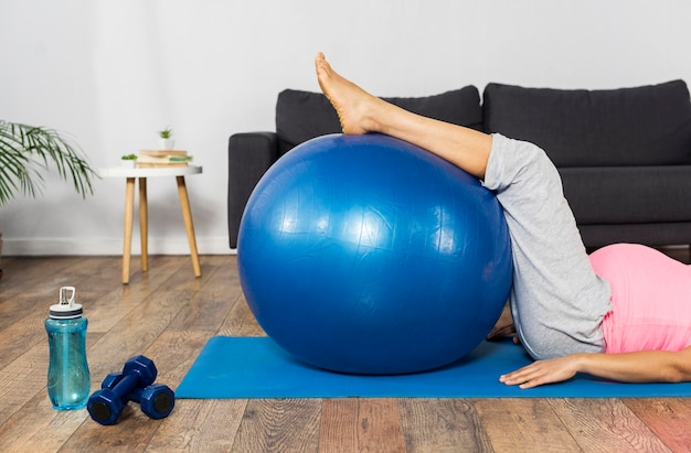 Kobieta w ciąży ćwiczy w domu z piłką i ciężarkami
