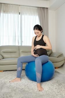 Kobieta w ciąży ćwiczy w domu