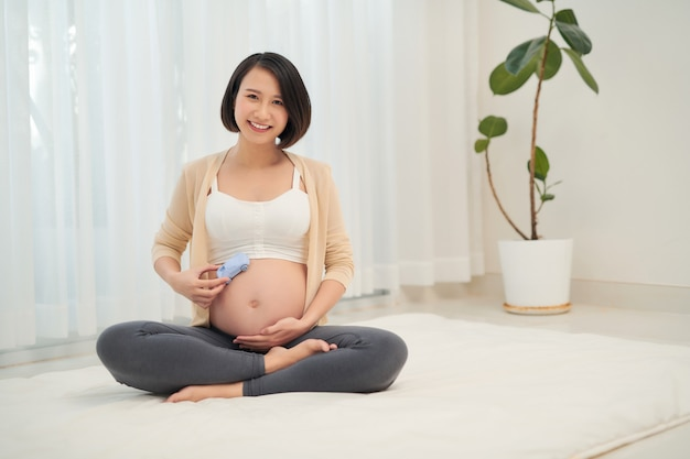 Kobieta w ciąży czeka chłopca z zabawką w ramionach