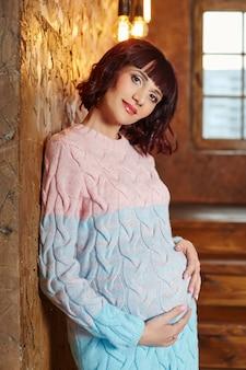 Kobieta w ciąży czeka na boże narodzenie w pobliżu choinki. ciąża i oczekiwanie na narodziny dziecka. macierzyństwo.