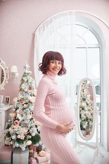 Kobieta w ciąży czeka na boże narodzenie w pobliżu choinki. ciąża