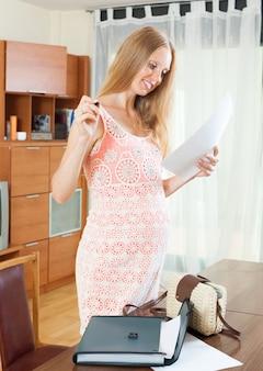 Kobieta w ciąży czytania dokumentu papierowego