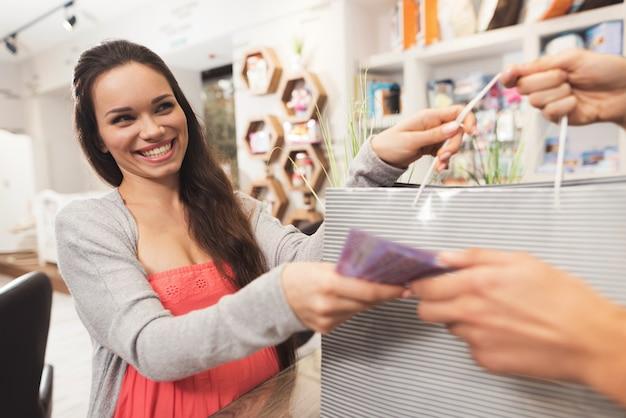 Kobieta w ciąży daje pieniądze sprzedawcy w sklepie.