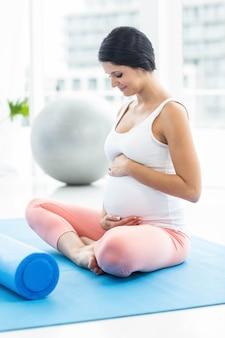 Kobieta w ciąży dotyka jej brzucha i uśmiecha się podczas ćwiczeń