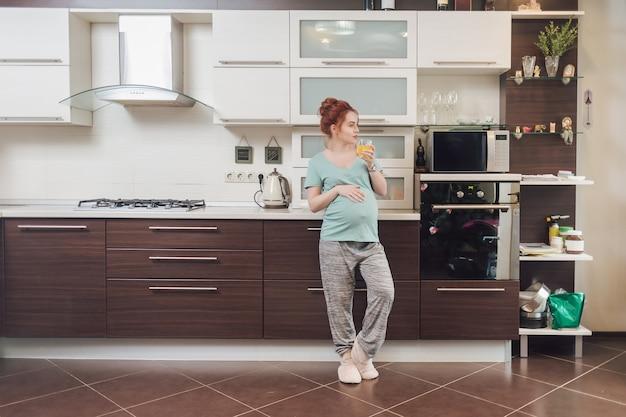 Kobieta w ciąży dotykając jej brzuch podczas picia soku