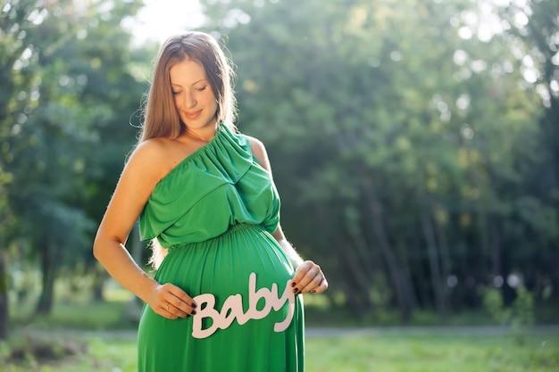Kobieta w ciąży gospodarstwa słowo dziecko