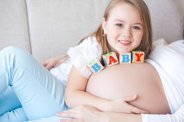 Kobieta w ciąży i jej córeczka zabawy w pomieszczeniu. macierzyństwo. młoda matka czeka na narodziny dziecka z małą uroczą córką. rodzina razem.