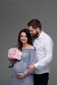 Kobieta w ciąży i jej mąż przytulają się na szarym tle w studio