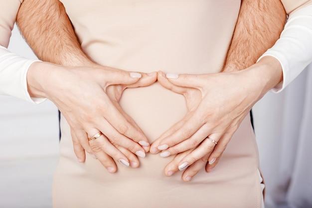 Kobieta w ciąży i jej mąż, trzymając się za ręce na brzuchu w ciąży