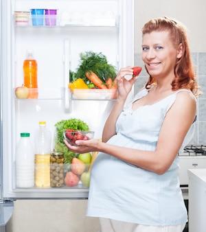 Kobieta w ciąży i lodówka ze zdrową żywnością warzywa i owoce
