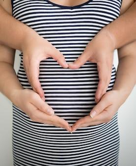 Kobieta w ciąży i mąż trzymający się za ręce w kształcie serca na brzuchu