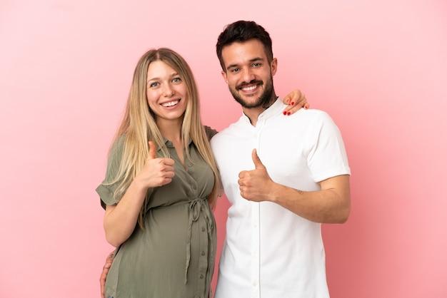 Kobieta w ciąży i mężczyzna na odosobnionym różowym tle dający kciuk w górę gestu