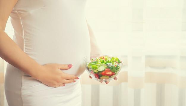 Kobieta w ciąży je sałatkę z warzywami