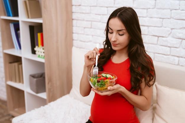 Kobieta w ciąży je sałatkę.
