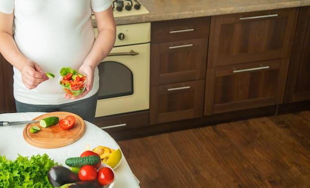 Kobieta w ciąży je warzywa i owoce