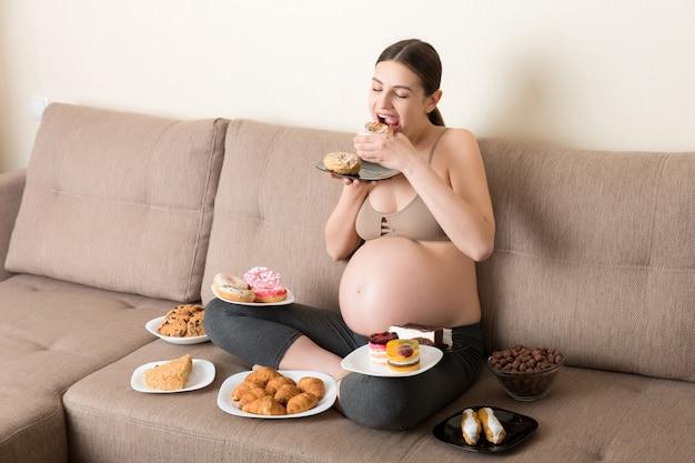 Kobieta w ciąży jedząca dużo niezdrowego jedzenia