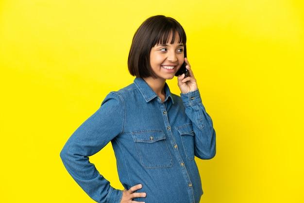 Kobieta w ciąży korzystająca z telefonu komórkowego na żółtym tle pozuje z rękami na biodrach i uśmiecha się