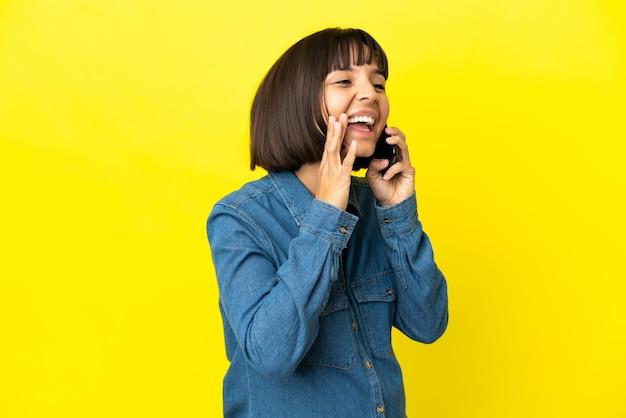 Kobieta w ciąży korzystająca z telefonu komórkowego odizolowanego na żółtym tle krzyczy z szeroko otwartymi ustami