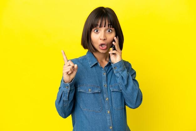 Kobieta w ciąży korzystająca z telefonu komórkowego odizolowanego na żółtym tle, zamierzająca zrealizować rozwiązanie, podnosząc palec w górę