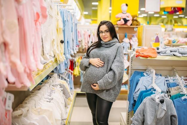 Kobieta w ciąży kupuje ubrania w sklepie dla noworodków. przyszła mama w sklepie z towarami dla niemowląt