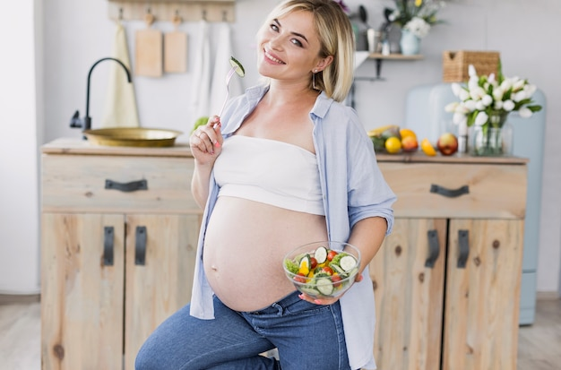 Kobieta w ciąży łasowania sałatka podczas gdy patrzejący kamerę