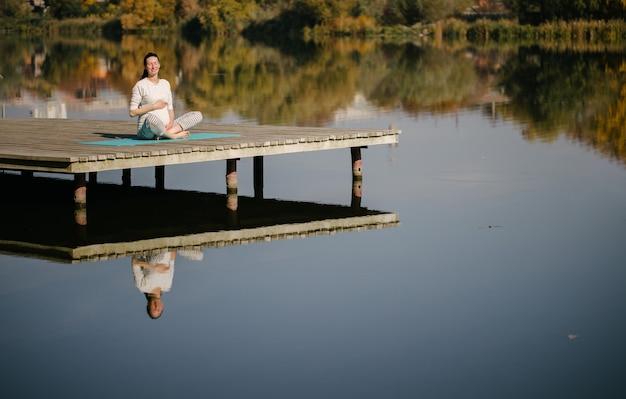 Kobieta w ciąży medytuje nad jeziorem trzymając brzuch w słoneczny jesienny dzień